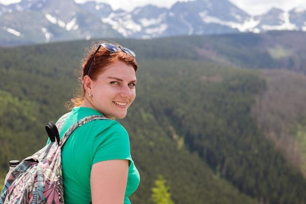 배낭을 가진 여성 여행자는 산 꼭대기에 앉아 카메라, 방황 여행 개념, 텍스트를위한 공간, 대기 서사시 순간을보고 있습니다.