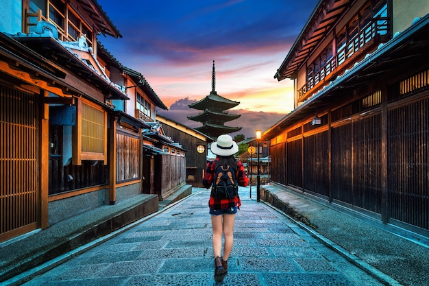 일본 교토의 야 사카 파고다와 산넨 자카 거리에서 배낭을 걷는 여성 여행자.