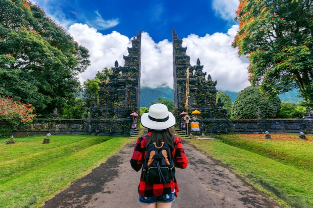Woman traveler with backpack walking at big entrance gate in bali, indonesia.