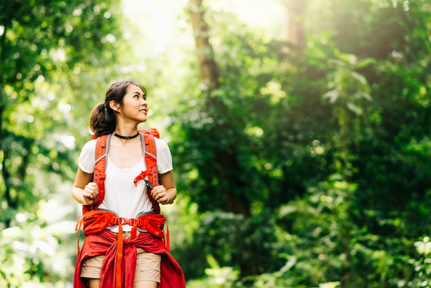 Woman traveler with backpack walking in forest
