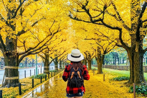 秋の黄色い銀杏の木の列を歩くバックパックを持つ女性旅行者。東京の秋の公園。