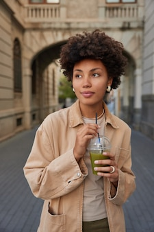 Woman traveler with curly bushy hair drinks green refreshing smoothie while walking in city wears fashionabe clothes strolls near ancient buildings