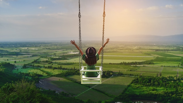 두 팔을 벌린 여성 여행자는 아름다운 풍경을 배경으로 그네를 탄다