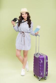 色の背景にパスポートとスーツケースを持つ女性旅行者
