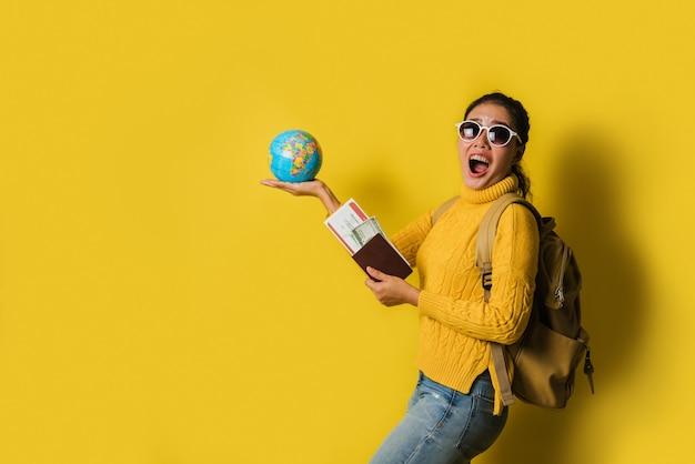 黄色の背景にパスポートとチケットを手にボールグローブを持って、スーツケースを持つ女性旅行者。幸せな女の子の笑顔の肖像画、世界中を旅するコンセプト。トラベルバックパック