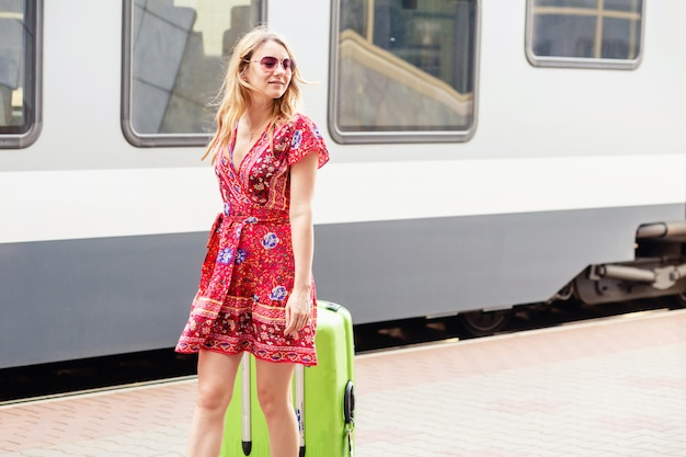 Woman traveler with suitcase on train station