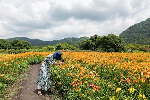 야외에서 타이거 릴리 농장에서 여행하는 여자