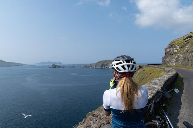 自転車で旅行している女性は、ディングル半島irの崖の彼女の携帯電話で写真を撮っています