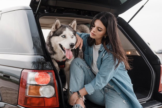 Woman traveling by car with her adorable husky dog