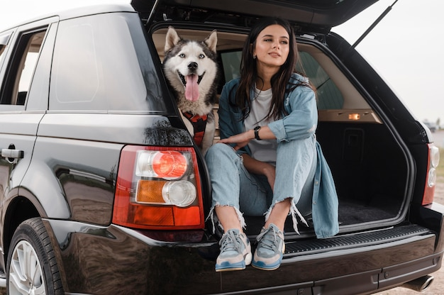 Woman traveling by car with her cute husky dog