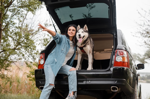 Woman traveling by car with her husky dog