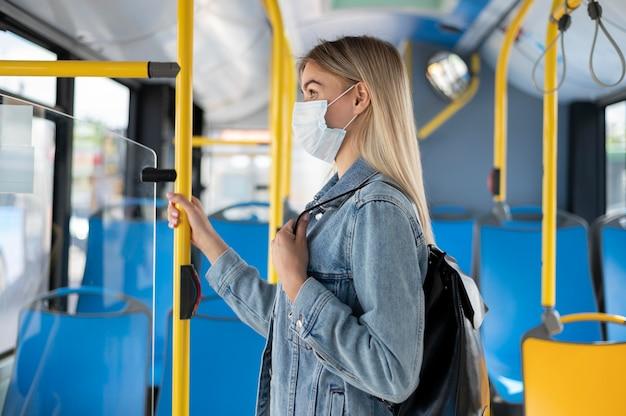 Женщина, путешествующая на общественном автобусе в медицинской маске для защиты