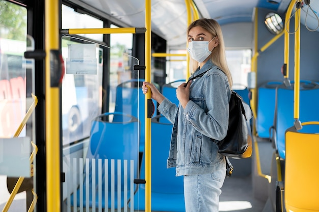 公共バスで旅行し、保護のために医療用マスクを着用している女性