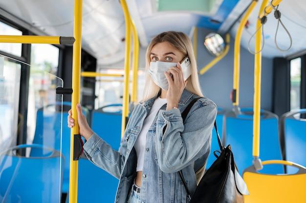 Женщина, путешествующая на общественном автобусе, разговаривает по телефону в медицинской маске для защиты