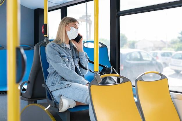 보호를 위해 의료 마스크를 쓰고 공중 버스로 여행하는 여성