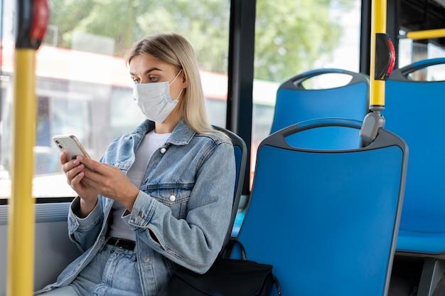 보호를 위해 의료 마스크를 쓰고 스마트폰을 사용하여 대중 버스로 여행하는 여성