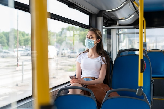 Женщина, путешествующая на общественном автобусе с использованием смартфона в медицинской маске для защиты