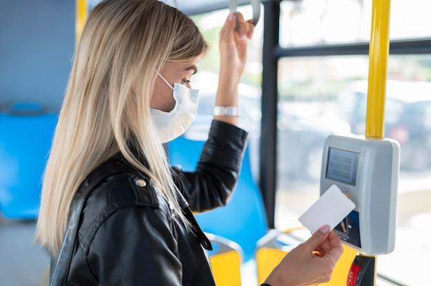 Donna che viaggia in autobus pubblico che indossa una maschera medica per protezione e usa il pass dell'autobus