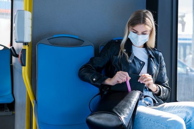 Donna che viaggia in autobus pubblico e indossa una maschera medica per protezione