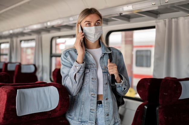Woman traveling by train and talking on the phone while wearing medical mask
