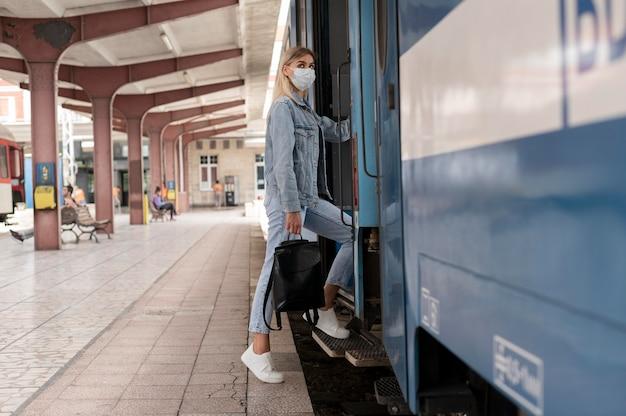 보호를 위해 의료용 마스크를 쓰고 기차로 여행하는 여성