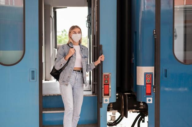 Donna che viaggia in treno indossando una maschera medica per protezione
