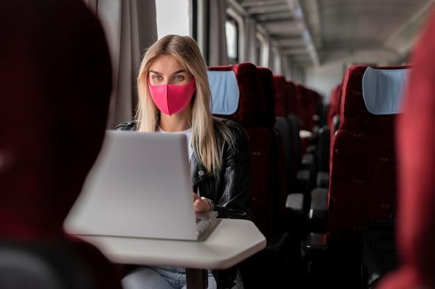 Donna che viaggia in treno e lavora al laptop