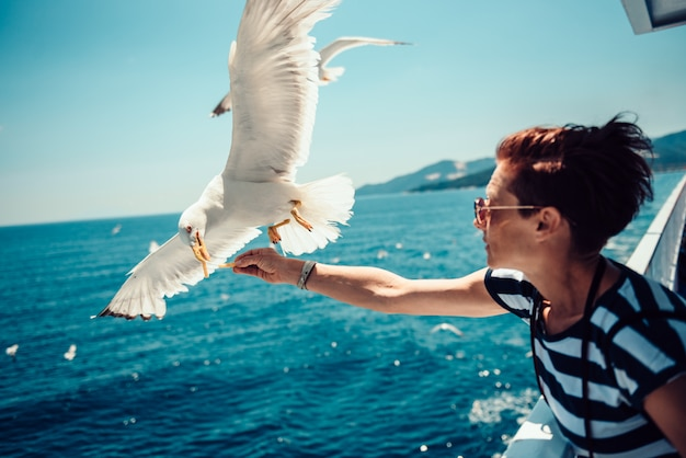 Woman traveling on ferryboat and feeding seagulls