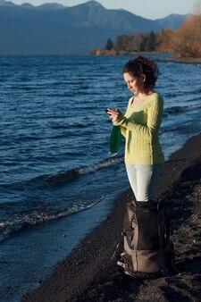 Женщина путешествует, держа в руке защитную маску и отправляя сообщение со своего мобильного телефона