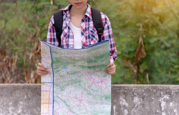 Женщина путешествует, держа и глядя карту