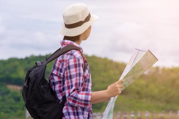 Женщина путешествуя держащ карту и смотрящ гору