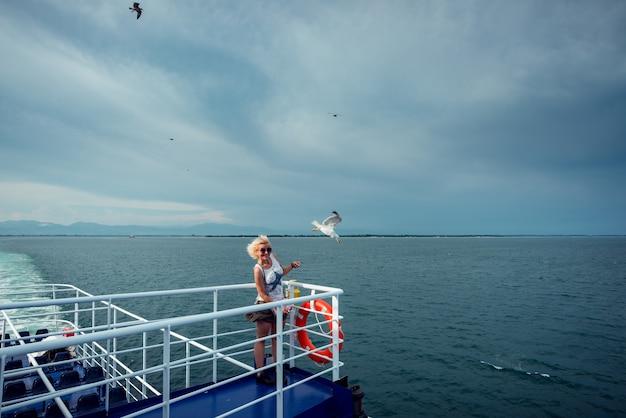 페리 보트를 타고 여행하는 여성과 데크 보드에서 보트 위로 날아가는 갈매기에게 먹이를 주는 여성
