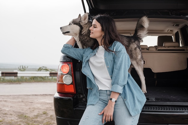 Woman traveling with her cute husky by car