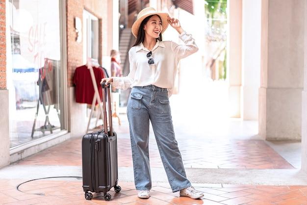 女性旅行者が空港で搭乗する乗客に歩いて黒いスーツケースの荷物バッグをドラッグ