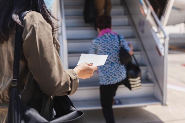 비행기에 탑승권을 들고 의료 마스크에 여자 여행자.
