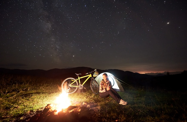 Woman traveller resting at night camping near burning campfire, illuminated tourist tent, mountain bike under beautiful evening sky full of stars