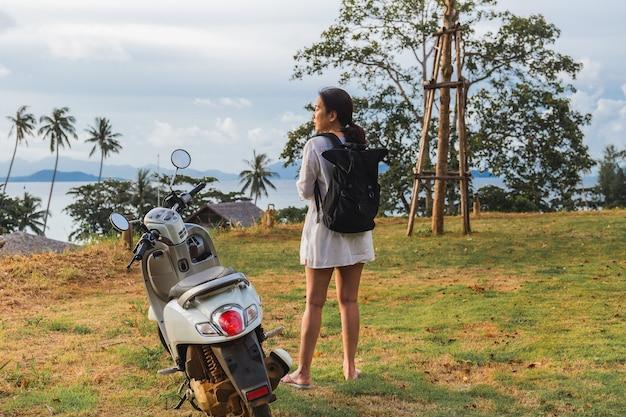 Путешественник женщина стоя возле мотоцикла на тропическом пляже.