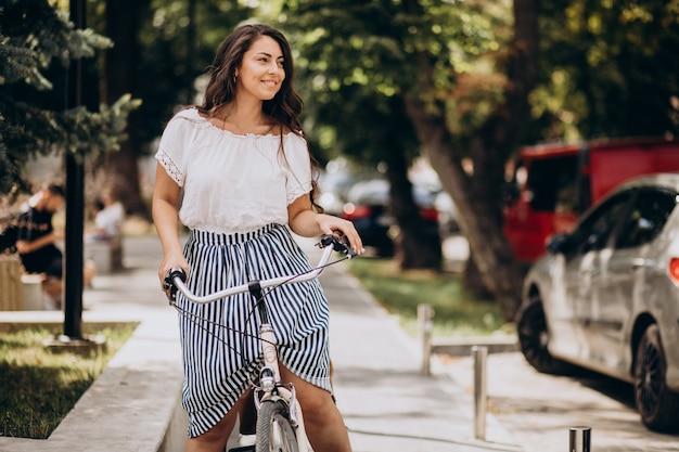 Donna che viaggia in bicicletta in città