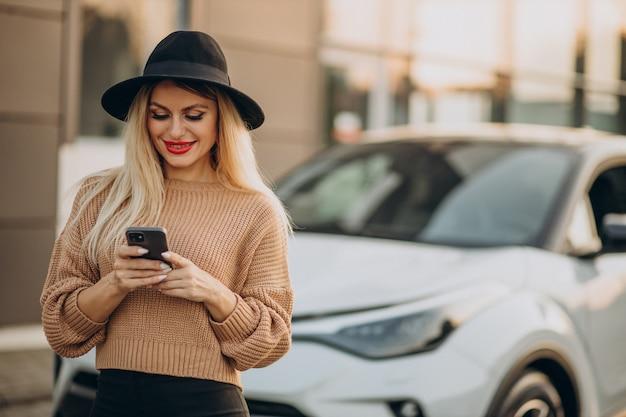 車で旅行し、電話を使用している女性
