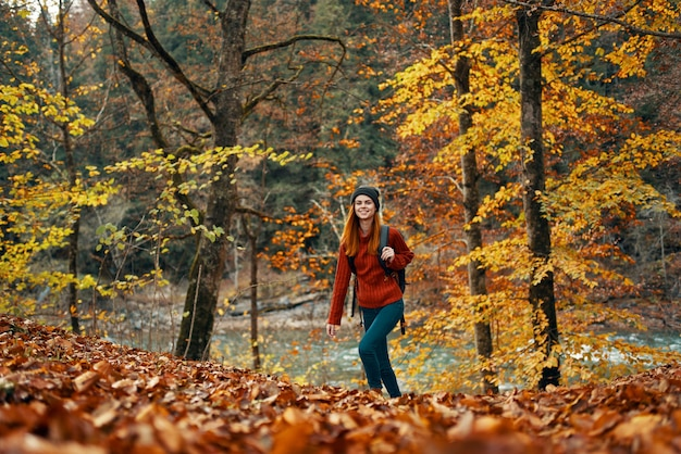 Woman travels in autumn forest in nature landscape yellow leaves on trees tourism river lake