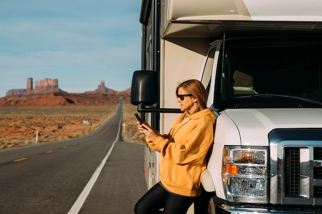 A woman travels by motorhome through monument valley in the usa desert and checks her mobile phone parked on the side of the road