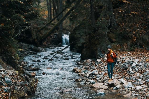 山の中の川を旅する女性と、背中にバックパックを背負った透明な水の森
