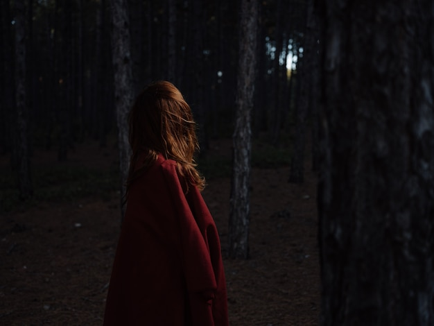 A woman travels in the forest at night with a red plaid on her shoulders, back view. high quality photo