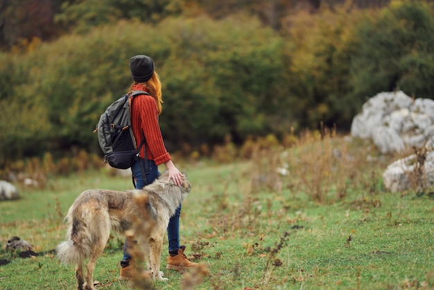 Женщина путешествует на природе с рюкзаком и собакой