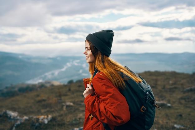 女性は山の風景のバックパックの赤いジャケットと帽子のモデルで旅行します