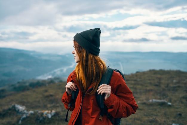 女性は山の風景を旅するバックパックの赤いジャケットと帽子のモデル