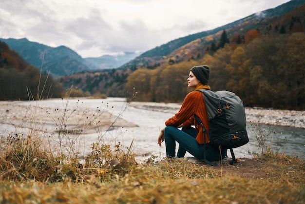 女性は森の残りの牧草地の川の近くの山を旅してリラックス