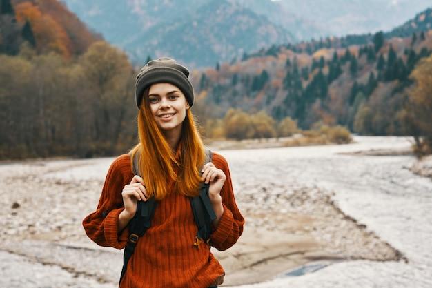 女性は屋外の新鮮な空気のビーチの川の風景の山々を旅行します