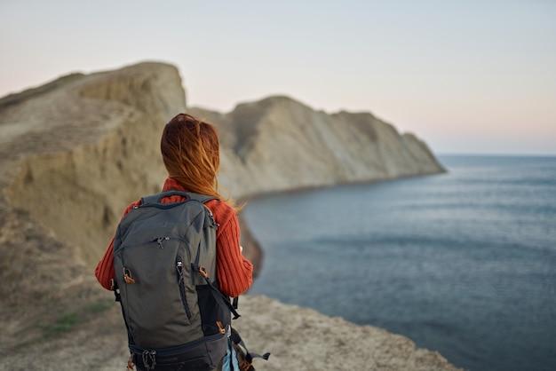 女性はバックパックで山を旅し、風景の新鮮な空気を歩きます。高品質の写真
