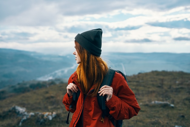 Woman travels in the mountains landscape backpack red jacket and hat model